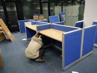 Công nhân tháo dỡ bàn ghế, đồ đạc để chuyển văn phòng